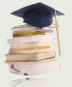 Black graduation cap positioned atop a pile of textbooks.